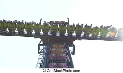 People riding on extreme attraction in amusement park. Happy friends having fun on thrilling roller coaster ride in amusement park