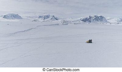 People riding on vintage snowmobile. Antarctica. - People...