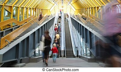 People rise and fall on the escalator in footbridge.