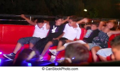 People rotates on mechanical amusement, closer view