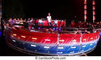 People rotating on platform of tagadance amusement -...