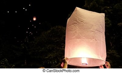 People run a large paper lantern with fire in the night sky...