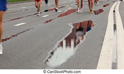 People run among puddles on asphalt with road marking at XXX Moscow International Peace Marathon