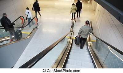 People run down steps of moving escalator - people run down...