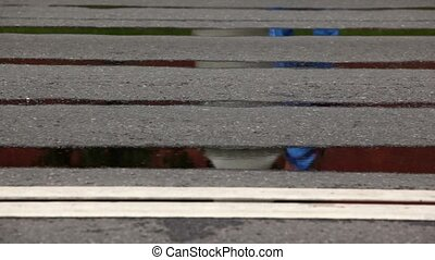 People run in both directions on asphalt with puddles