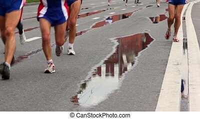 People run in sport wear and jogging shoes on wet asphalt with road marking
