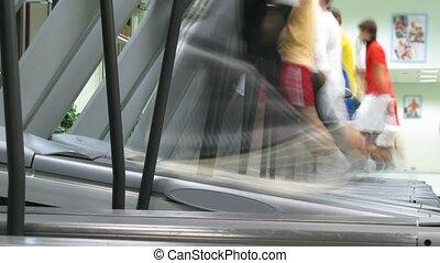 People run on treadmills at fitness club