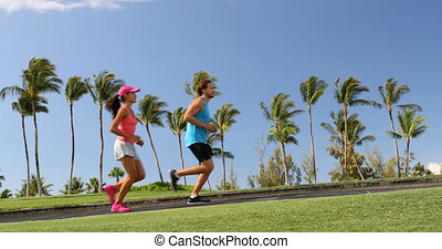 People running exercising on path in beautiful neighborhood with palm trees