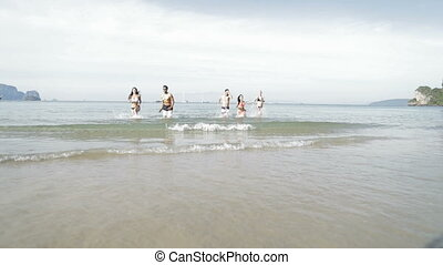 People Running From Water On Beach, Young Man And Woman Group Tourists