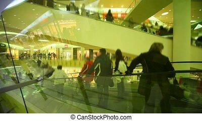people rushing on escalators in big multistorey mall shop