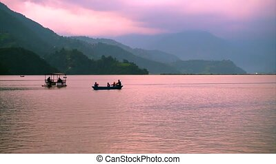 People sail in boats on Pheva lake against the background of...