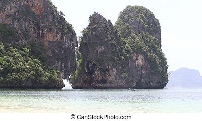 people sail in kayak near rock islands in blue sea