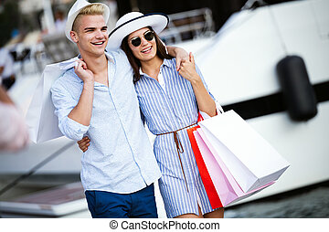 People, sale, love and happiness concept. Portrait of a couple with shopping bags in the city.