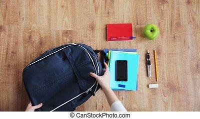 hands packing schoolbag - people, school supplies, education...