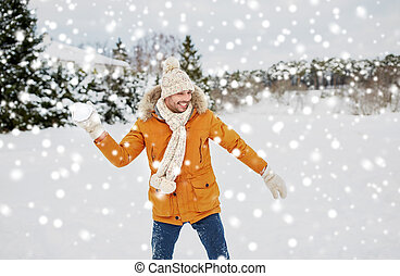 happy young man playing snowballs in winter