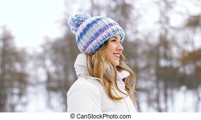 portrait of happy smiling woman outdoors in winter - people,...