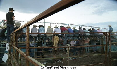 People seated and watching as spectators - A hand held wide...
