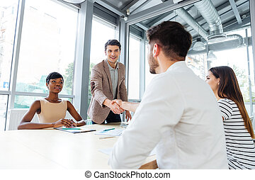 People shaking hands on business meeting in office