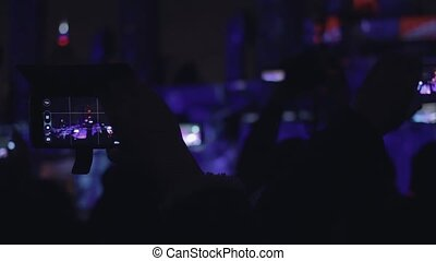 People shoots 3D mapping light show on a mobile phone. Hands...