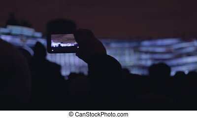 People shoots 3D mapping light show on a mobile phone. -...