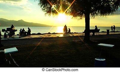 People Silhouette near the Seaside in Sunset