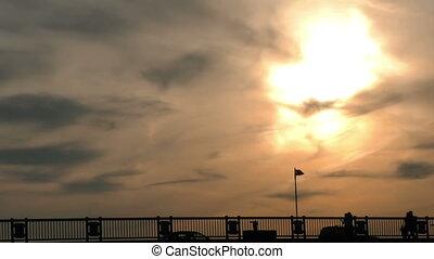 People Silhouette on Bridge and Sun