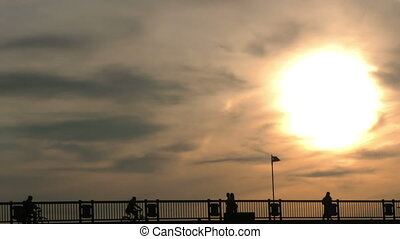 People Silhouette Passing on Bridge and Sunset