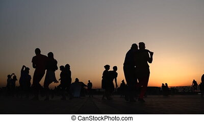 People silhouettes learning how to dance on quay at sunset - super slow motion