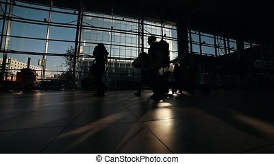 People silhouettes walking on the airport hall