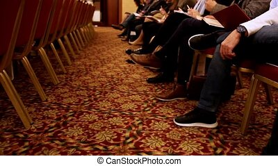 People sit and listen to the conference or presentation, workshop, master class - legs and arms, close up