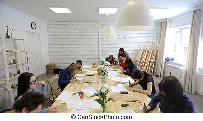 People sit around wooden table and draw some pictures in studio