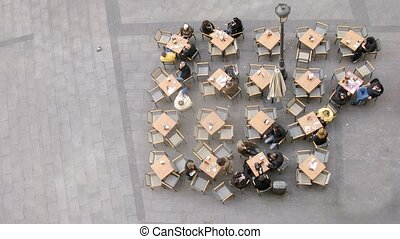 People sit at cafe little tables on street, time lapse