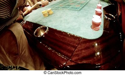 People sit at table with chips and stake, close-up.