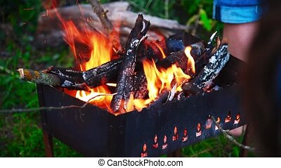People sit by the fire and periodically turning over burning...
