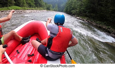 Rafting. People sit in an inflatable rubber boat with oars and float down mountain river. POV. View back of front man sitting in boat. Travel activities outdoor. Mountain landscapes, mountain scenery