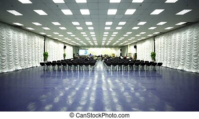 People sit on conference hall, view far from behind