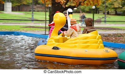 People sits in toy ducks on water in amusement park