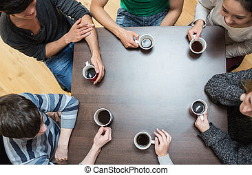 People sitting around table drinking coffee - Students...