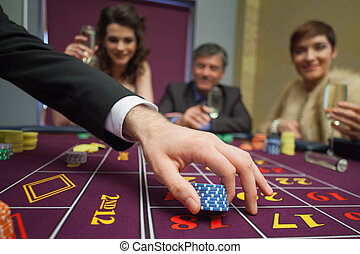 People sitting at the table placing bets