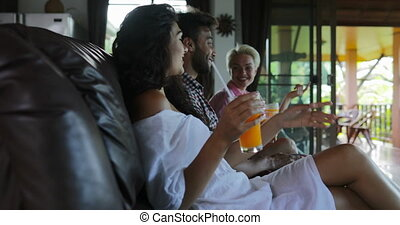 People Sitting On Coach Watch Tv In Living Room Drink Orange...