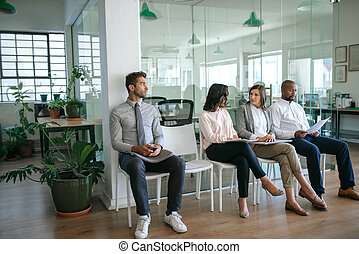 People sitting together in an office waiting for interviews