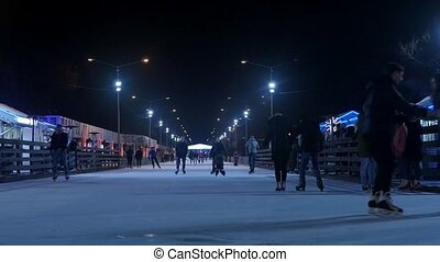 people skate on the rink in the Park