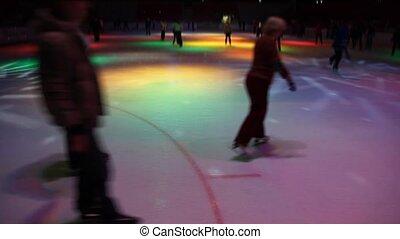 people skating in night skating rink with dynamic...