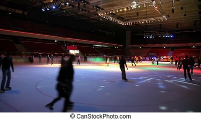 people skating in roofed skating rink with dynamic illumination
