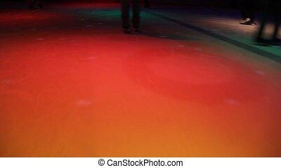 people skating in skating rink with illumination, camera...