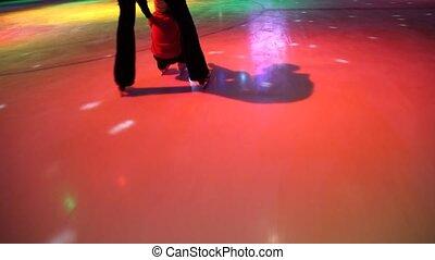 people skating in skating rink with illumination, camera moving