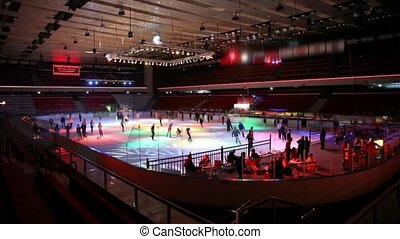 people skating on ice in roofed skating rink with dynamic illumination