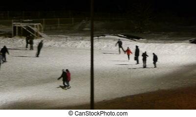 People skating on ice-rink, night view - People skating on...