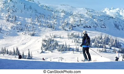 Many people ski past on sunny slope high in the mountains