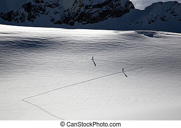 People ski touring in the swiss alps on a glacier